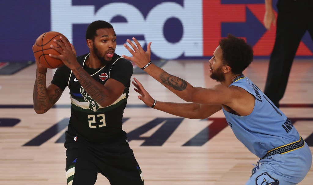Milwaukee Bucks guard Sterling Brown (23) holds the ball away from Memphis Grizzlies forward Kyle Anderson (1) in the second half of an NBA basketball...