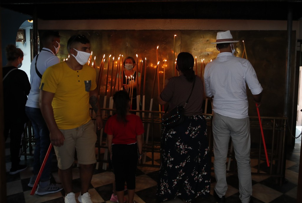 Pilgrims light candles at the Holy Church of Panagia of Tinos, on the Aegean island of Tinos, Greece, on Saturday, Aug. 15, 2020. For nearly 200 years...