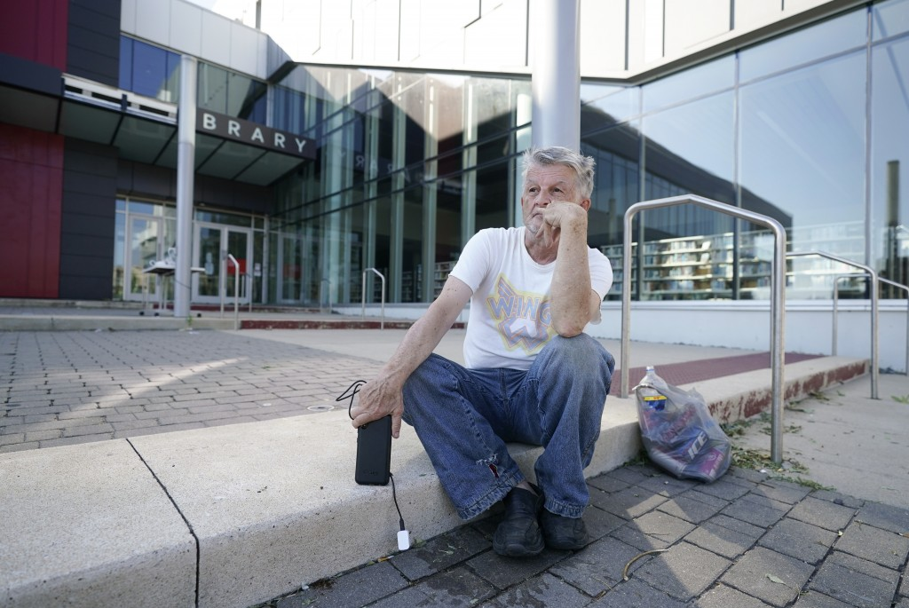 Jerry Frajman sits in front of the Cedar Rapids Public Library after charging his cell phone, Friday, Aug. 14, 2020, in Cedar Rapids, Iowa. The storm ...
