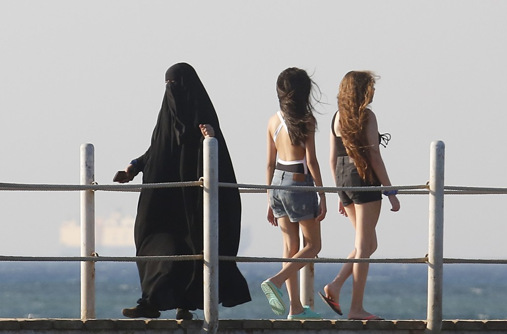 FILE - In this July 26, 2019 file photo, holiday makers walk at al Sokhna beach in Suez, Egypt. The burkini, a swimsuit worn by conservative Muslims t...