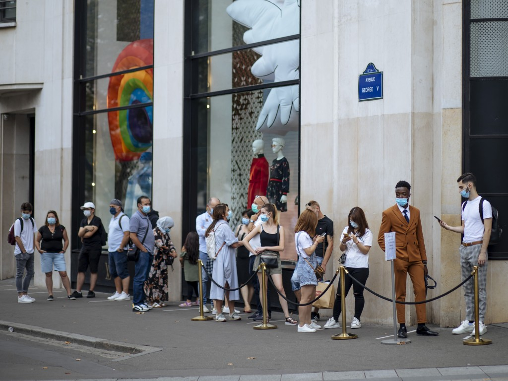People with face masks queue as they wait to get in the Louis Vuitton shop on the Champs Elysee avenue in Paris, Saturday, Aug. 15, 2020. Paris extend...