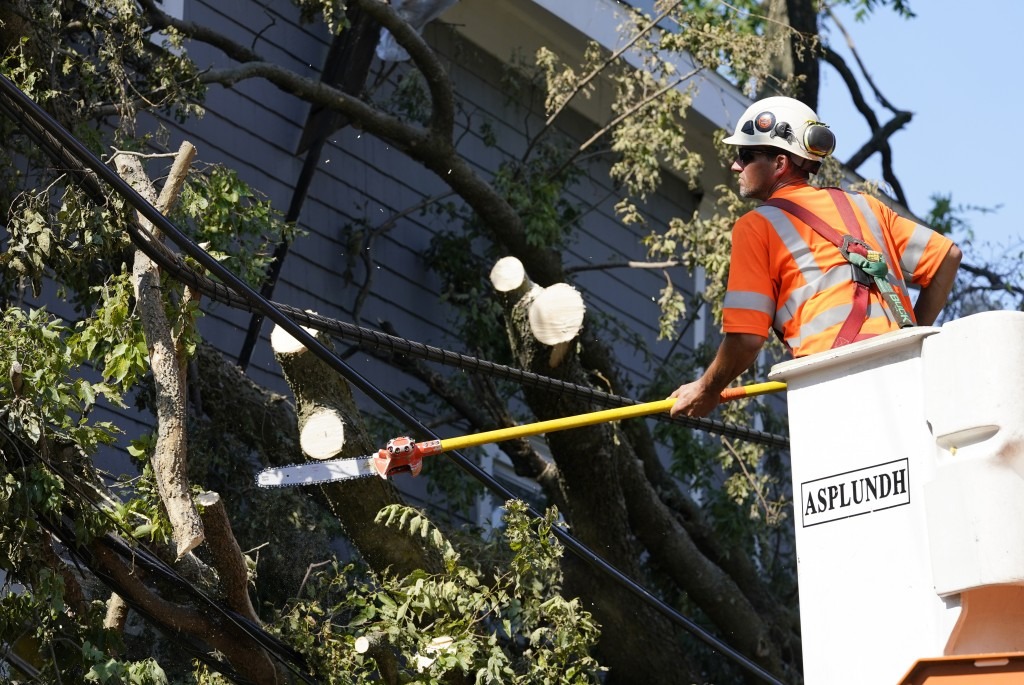 A worker trims a tree brunch around power line, Friday, Aug. 14, 2020, in Cedar Rapids, Iowa. The storm that struck Monday morning left tens of thousa...