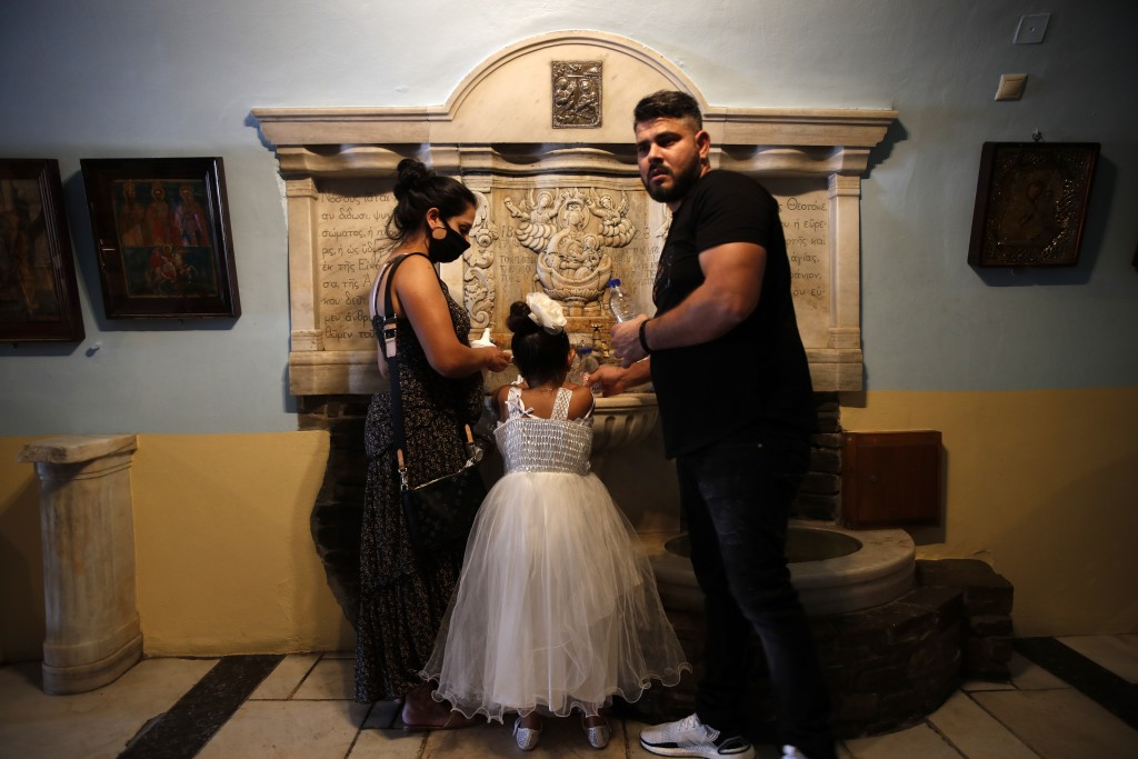 A family fills holy water at the Holy Church of Panagia of Tinos, on the Aegean island of Tinos, Greece, on Thursday, Aug. 13, 2020. For nearly 200 ye...