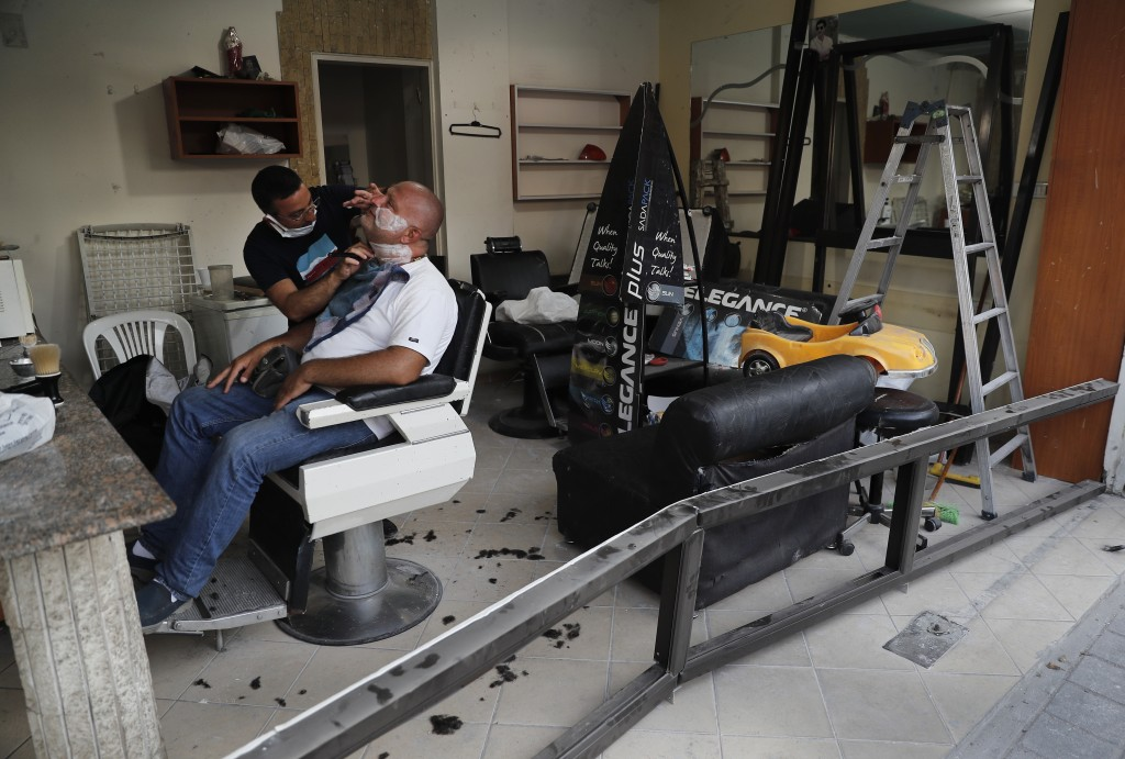 A Lebanese barber shaves the beard of a customer, at a men salon that damaged by last week's explosion that hit the seaport of Beirut, in the middle o...