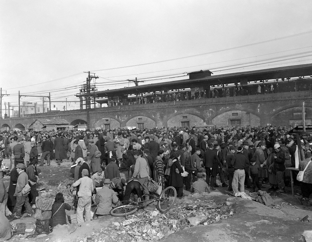 FILE - In this Dec. 16, 1945, file photo, a crowd gathers at Shimbashi railroad station in Tokyo for a hunger demonstration by residents of the city. ...