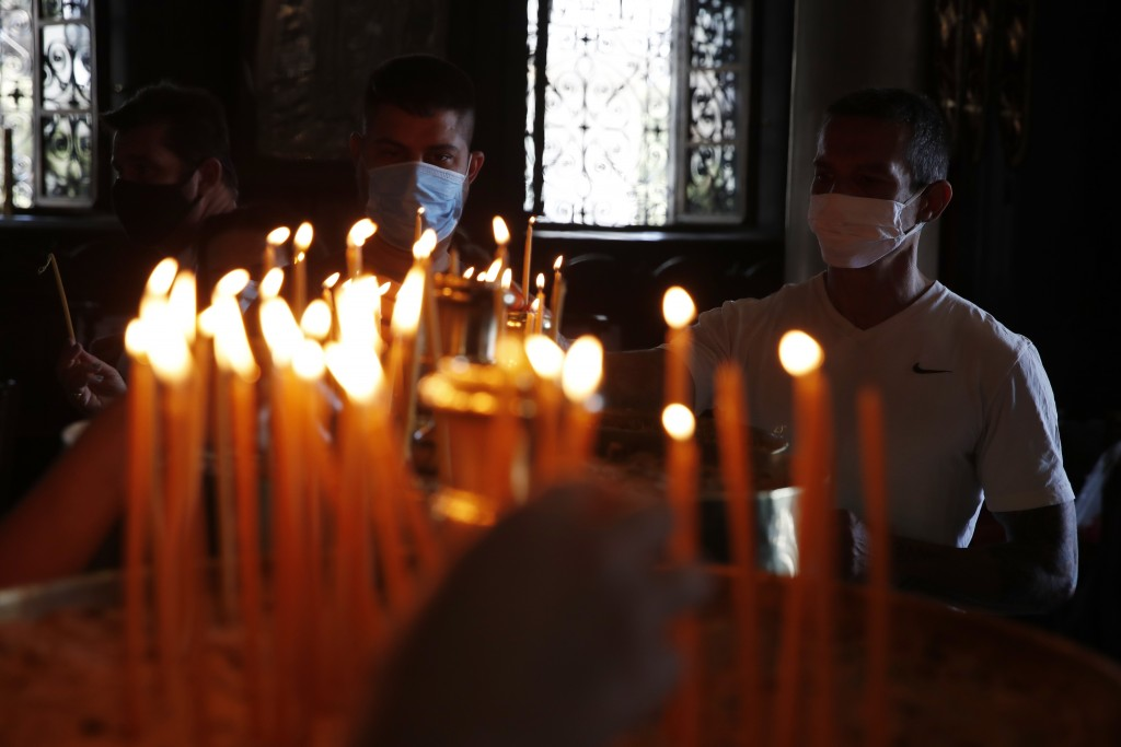Pilgrims wearing face masks against the spread of the new coronavirus, light candles in the Holy Church of Panagia of Tinos, on the Aegean island of T...