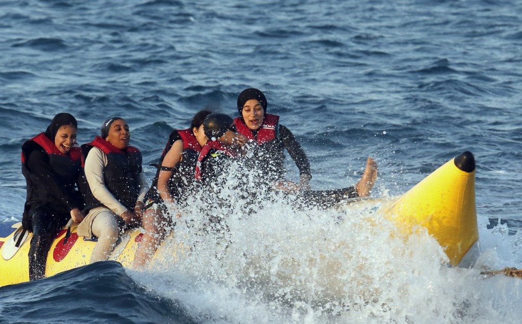FILE - In this July 26, 2019 file photo, holiday-makers ride a banana boat at al Sokhna beach in Suez, Egypt. The burkini, a swimsuit worn by conserva...