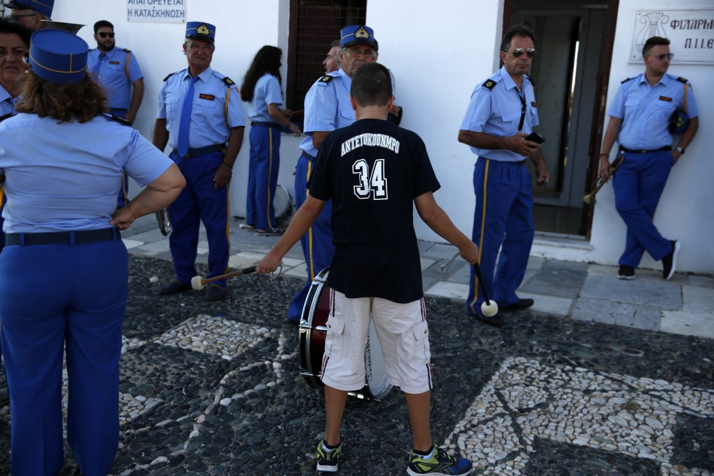 A boy plays with the drumsticks as the Philharmonic band stands outside the Holy Church of Panagia of Tinos, on the Aegean island of Tinos, Greece, on...