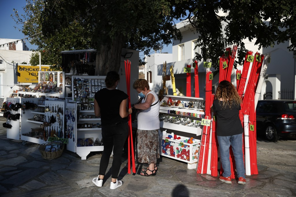 A woman wearing a face mask against the spread of the new coronavirus, buys candles outside the Holy Church of Panagia, on the Aegean island of Tinos,...
