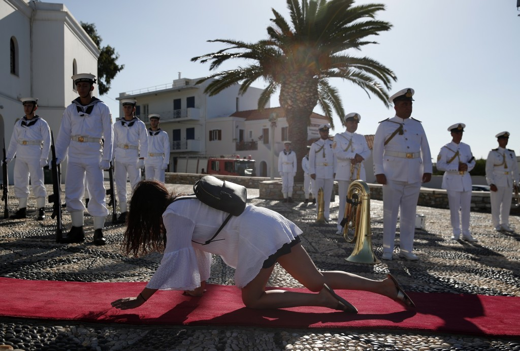 A pilgrim crawls in front of the Navy band outside the Holy Church of Panagia of Tinos, on the Aegean island of Tinos, Greece, on Saturday, Aug. 15, 2...