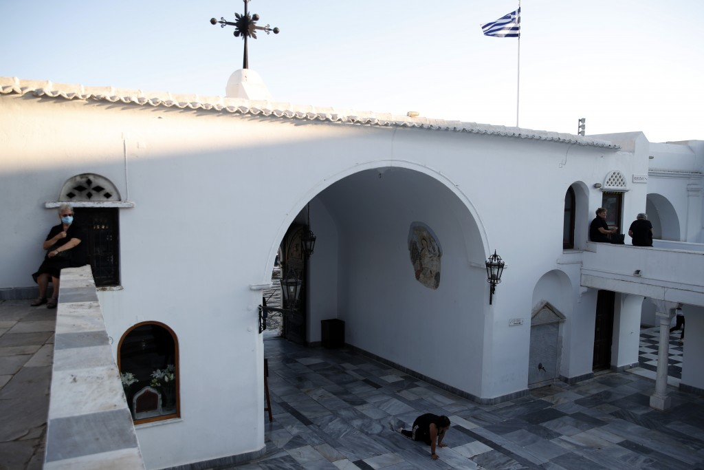 A woman crawls as other pilgrims sit at the yard of the Holy Church of Panagia of Tinos, on the Aegean island of Tinos, Greece, on Thursday, Aug. 13, ...