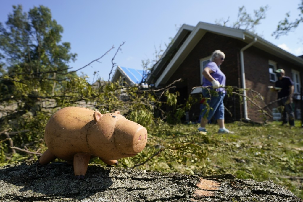 A toy sits on a log as a woman moves branches from a fallen tree to the curb, Friday, Aug. 14, 2020, in Cedar Rapids, Iowa. The storm that struck Mond...