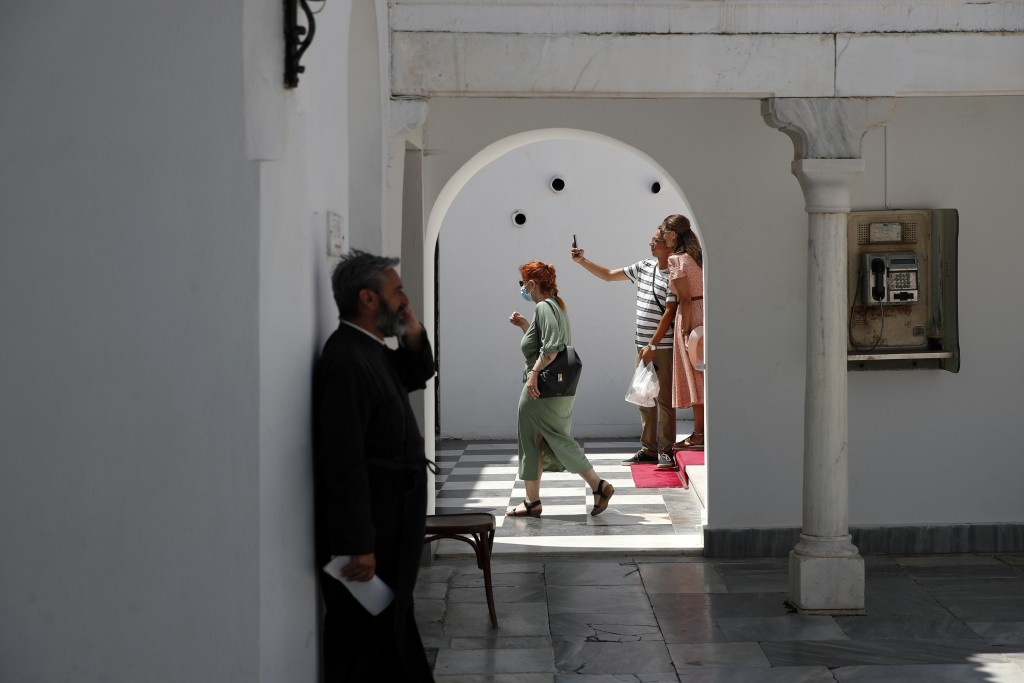 A woman wearing a face mask against the spread of the new coronavirus, leaves the Holy Church of Panagia of Tinos as a couple takes a photograph, on t...