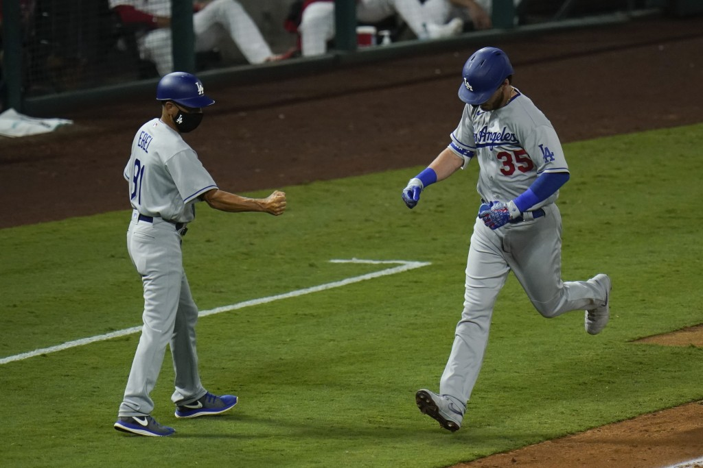 Los Angeles Dodgers' Cody Bellinger, right, celebrates his two-run home run with third base coach Dino Ebel during the sixth inning of a baseball game...