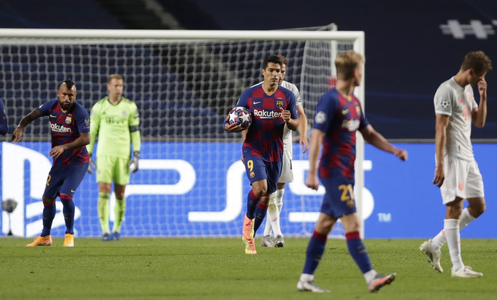 Barcelona's Luis Suarez, center, carries a ball after scoring his sides second goal past Bayern's goalkeeper Manuel Neuer, back, during the Champions ...