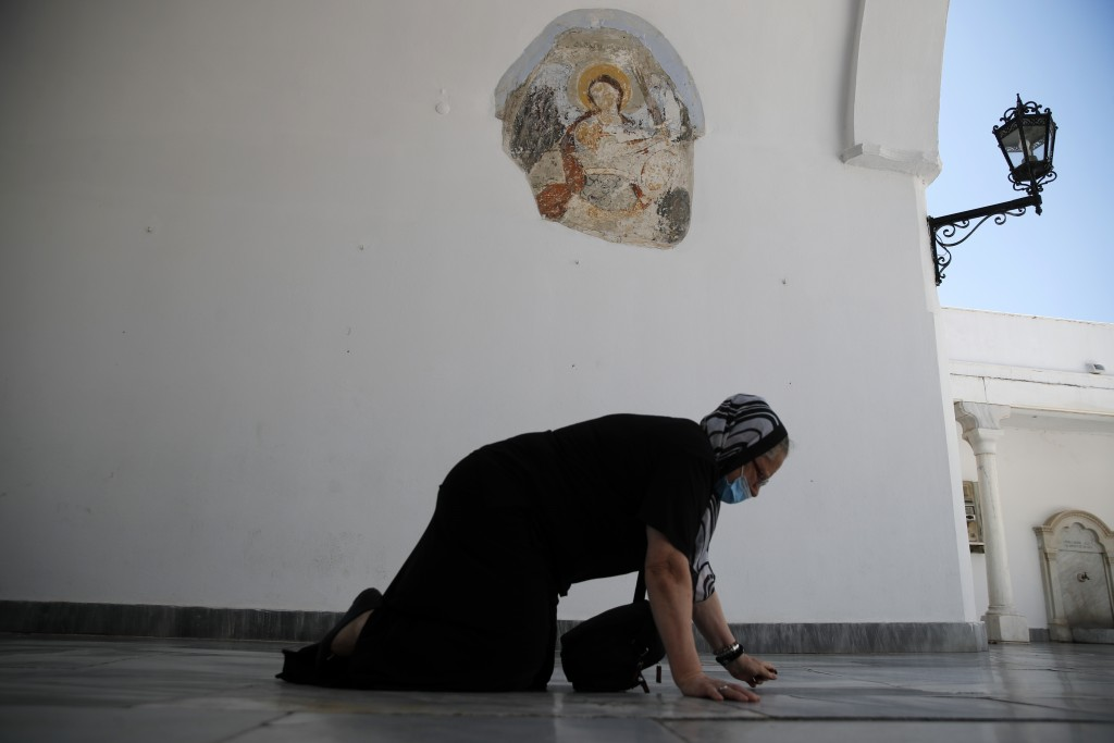An elderly woman crawls as she enters the entrance of the Holy Church of Panagia of Tinos, on the Aegean island of Tinos, Greece, on Thursday, Aug. 13...
