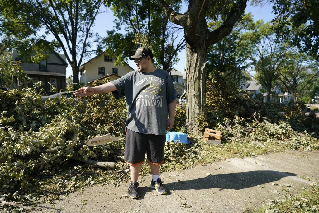 Eric Fish takes a break from hauling downed branches in front of his home, Friday, Aug. 14, 2020, in Cedar Rapids, Iowa. The storm that struck Monday ...