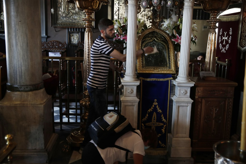 A worker cleans an icon believed to perform miracles as a pilgrim crawls inside the Holy Church of Panagia of Tinos, on the Aegean island of Tinos, Gr...