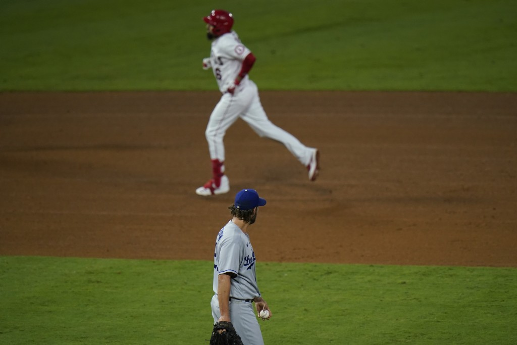 Los Angeles Dodgers starting pitcher Clayton Kershaw, bottom, stands near the mound after giving up a home run against Los Angeles Angels' Anthony Ren...