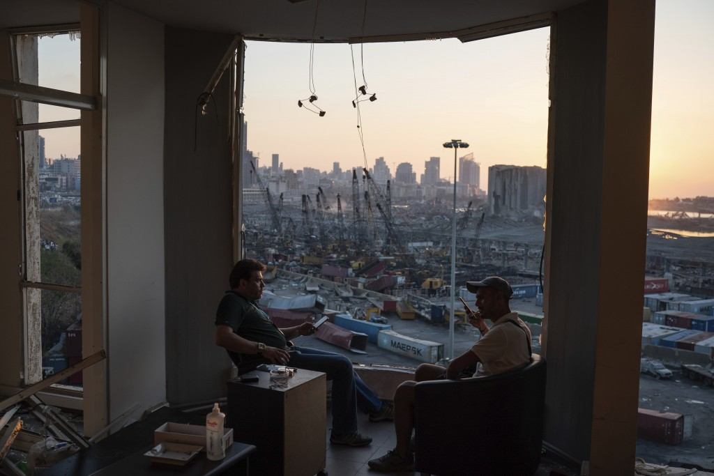 Two men sit on the destroyed balcony of a building facing the site of last week's massive explosion in the port of Beirut, Lebanon, Friday, Aug. 14, 2...
