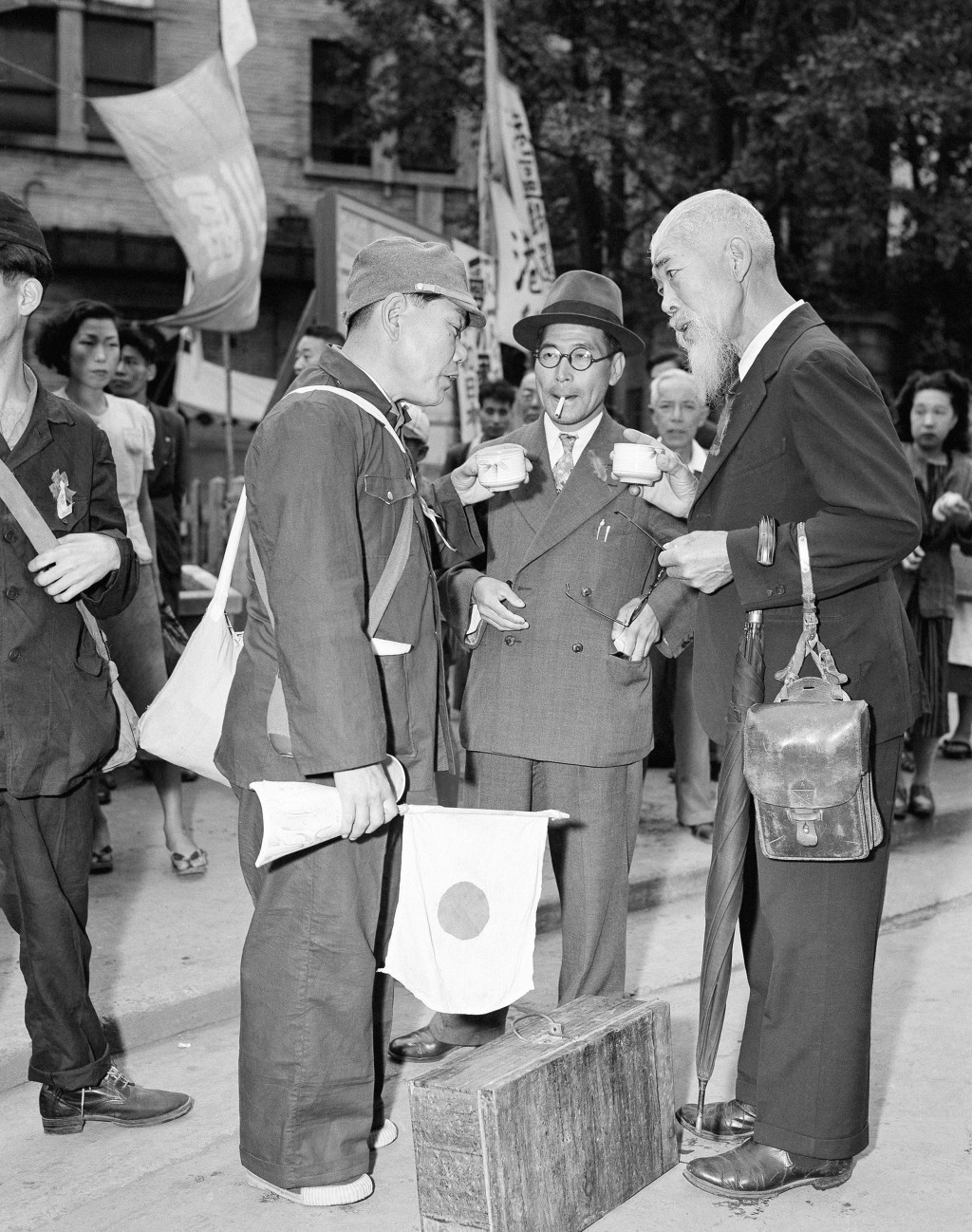 FILE - In this Oct. 7, 1949, file photo, relatives meet one of the Japanese repatriates from Manchuria and have cups of hot tea supplied by the Japane...