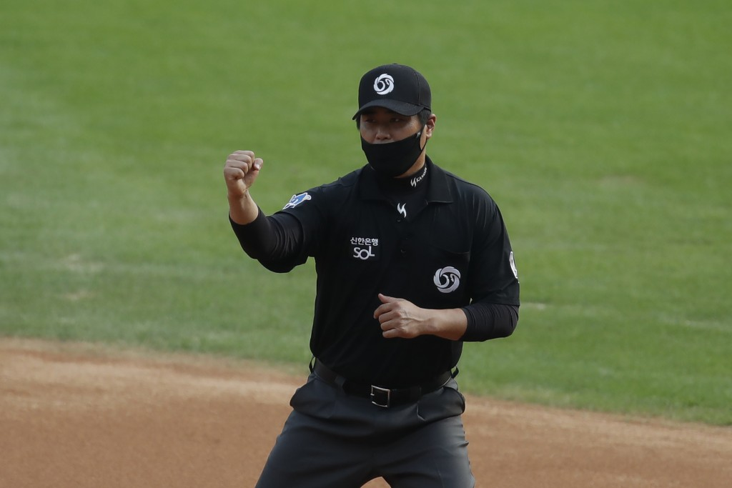 First base umpire Kim Seon-soo, wearing a mask as a precaution against the coronavirus, makes a call during the KBO league baseball game between KT Wi...