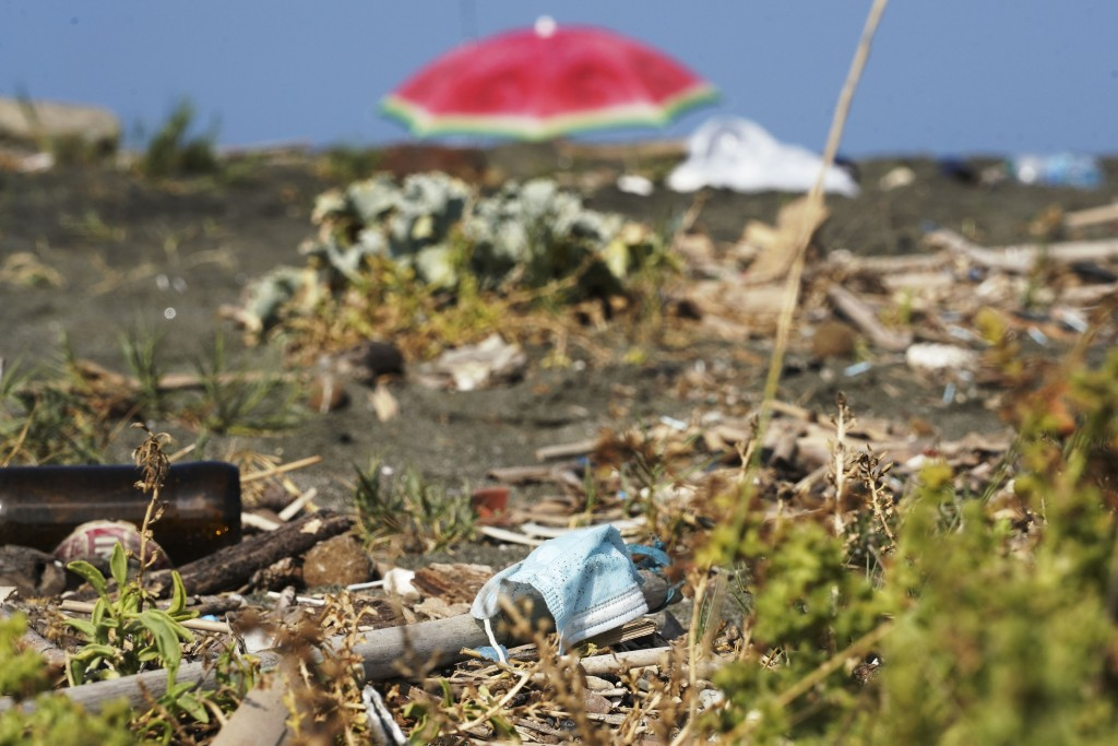 A protective mask is seen among other garbage on a beach at Fiumicino, near Rome, Saturday, Aug. 15, 2020. Italy produced 10% less garbage during its ...