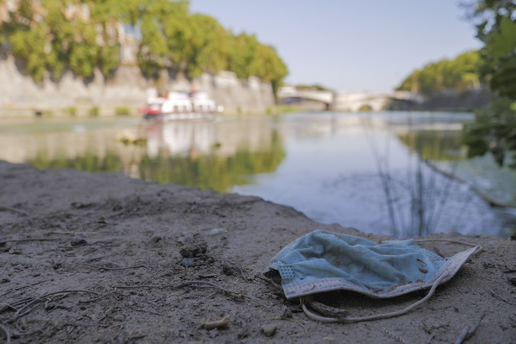 A protective mask is seen on the ground on Rome's Tiber river banks, in Rome, Wednesday, Aug. 12, 2020. Italy produced 10% less garbage during its cor...