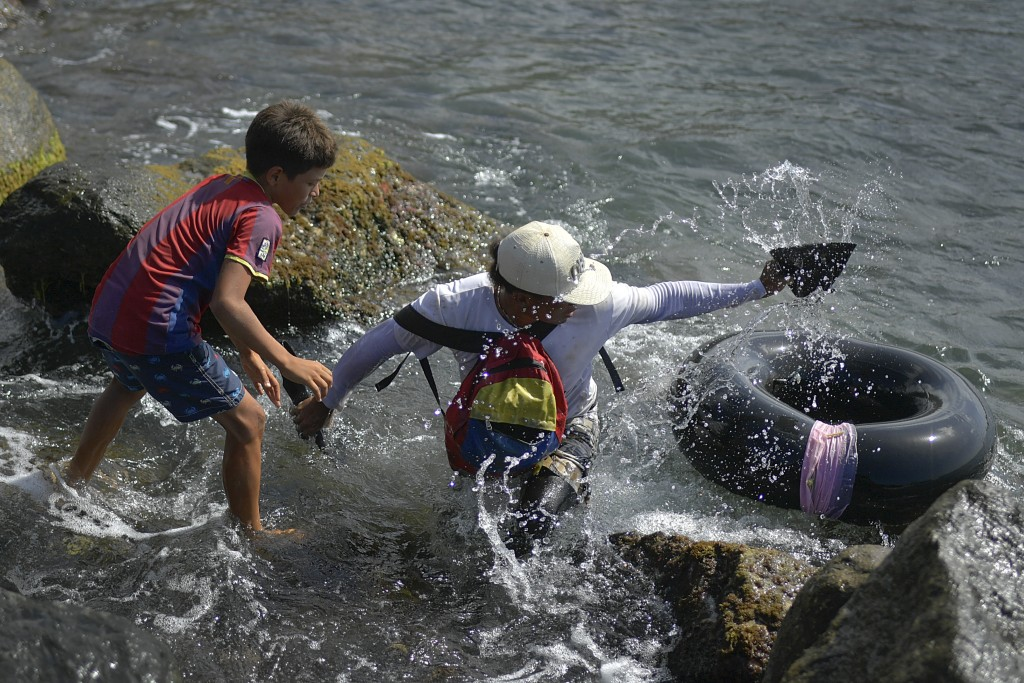 Jonny Gomez, a 22-year-old bricklayer by trade, returns to shore after a day of open sea fishing on his inner tube, at Playa Escondida in La Guaira, V...