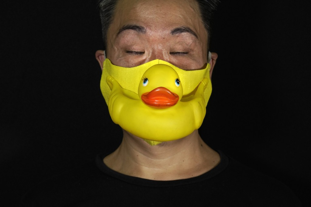 Edmond Kok, a Hong Kong theater costume designer and actor, wearing a face mask made by a rubber yellow duck in Hong Kong Thursday, Aug. 6, 2020. With...