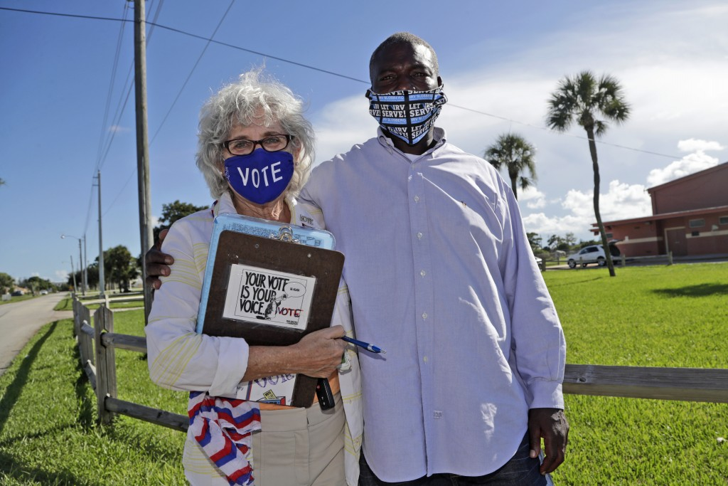 William Freeman, 51, right, poses for a photograph with Arlene Ustin, of the League of Women Voters in Palm Beach County, left, outside of his polling...