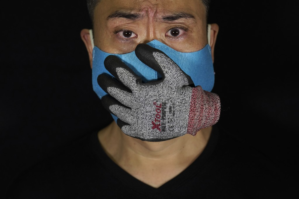 Edmond Kok, a Hong Kong theater costume designer and actor, wearing a face mask designed with a stuffed glove stuck on it, representing a hand over hi...