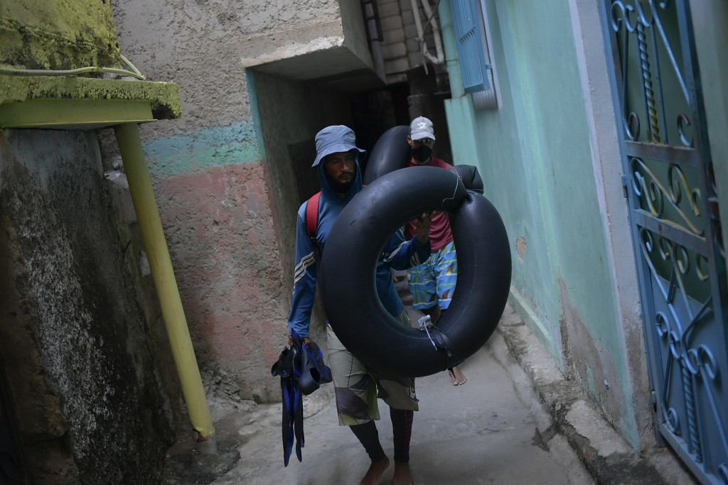 Jean Carlos Almeida, 35, and Eric Mendez, 40, return home after a day of open sea fishing on their inner tubes, at Playa Escondida in La Guaira, Venez...