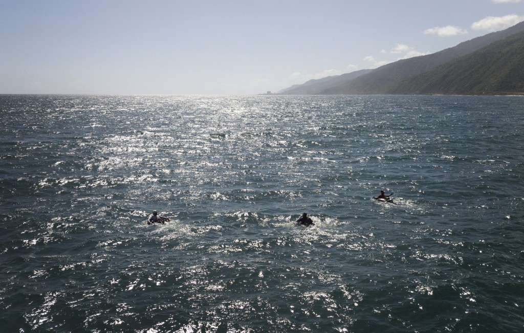 A group of bricklayers by trade float on their inner tubes in fishing in the open sea to fish at Playa Escondida in La Guaira, Venezuela, Friday, Aug....