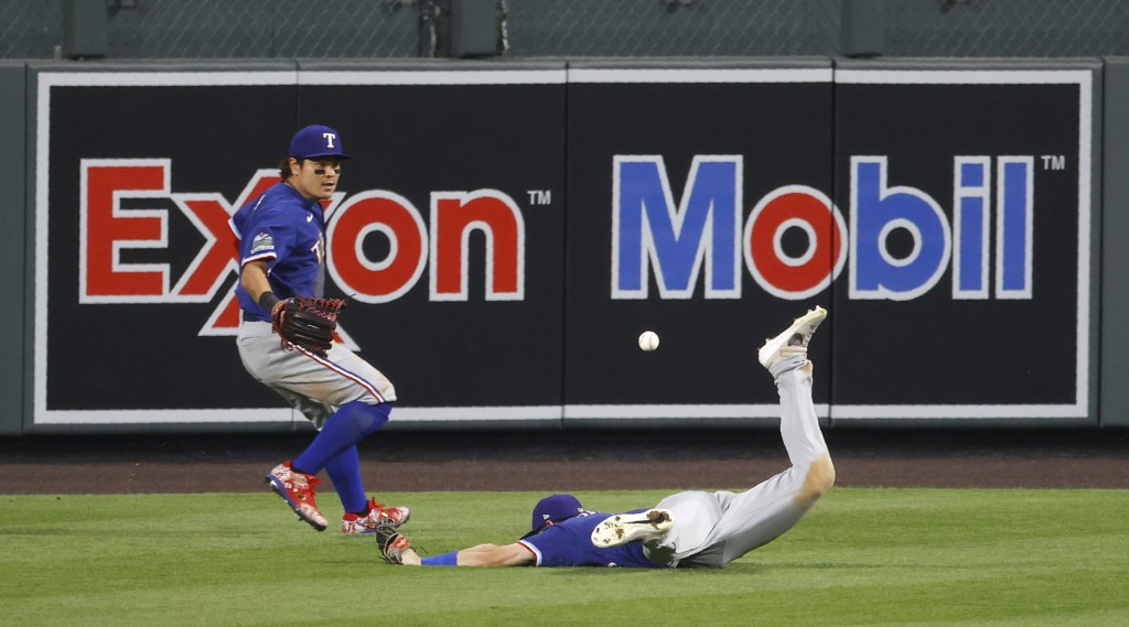 Texas Rangers center fielder Nick Solak, right, misses a ball that landed for a triple by Colorado Rockies' Charlie Blackmon, as Rangers left fielder ...