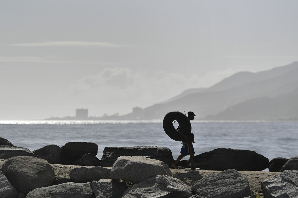 Edward Murat, 20, carries his inner tube to the beach for a day of open sea fishing at Playa Escondida in La Guaira, Venezuela, Friday, Aug. 14, 2020....