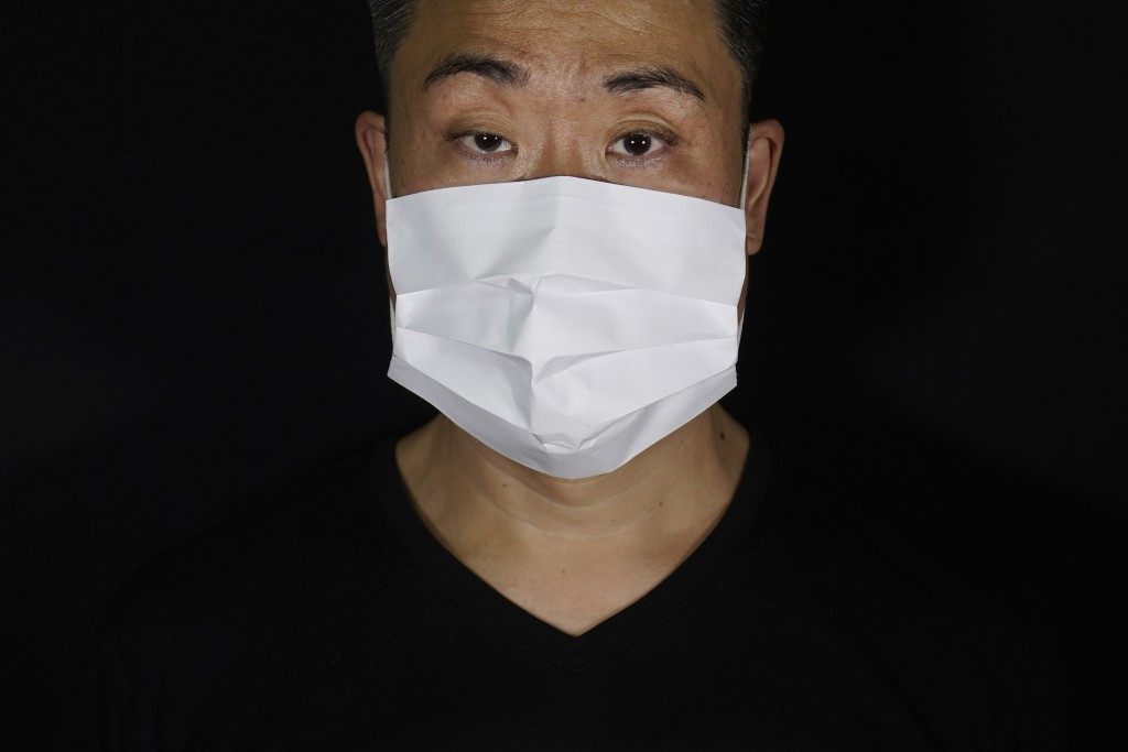 Edmond Kok, a Hong Kong theater costume designer and actor, wearing a face mask made by a white paper in Hong Kong Thursday, Aug. 6, 2020. With little...