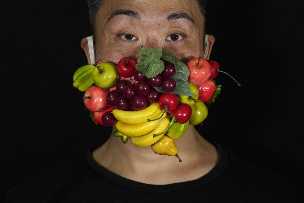 Edmond Kok, a Hong Kong theater costume designer and actor, wearing a face mask decorated with many different fruits in Hong Kong Thursday, Aug. 6, 20...