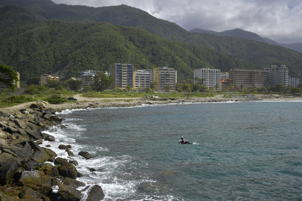 Jonny Gomez, a 22-year-old bricklayer by trade, returns from a day of open sea fishing on his inner tube, at Playa Escondida in La Guaira, Venezuela, ...