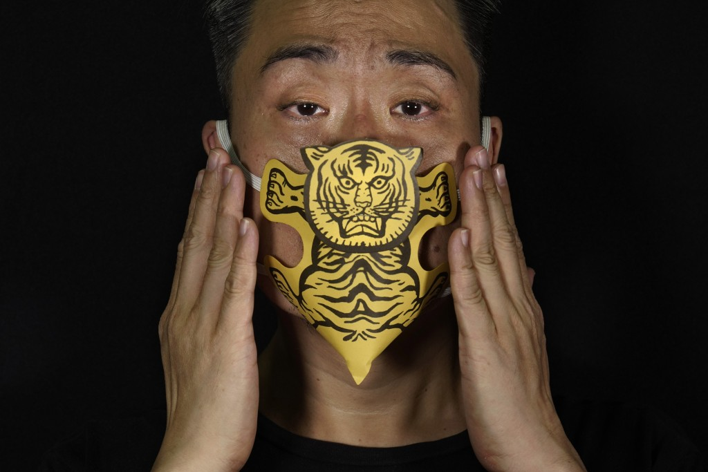 Edmond Kok, a Hong Kong theater costume designer and actor, wearing a face mask made by a paper tiger use for villain hitting in Hong Kong Thursday, A...