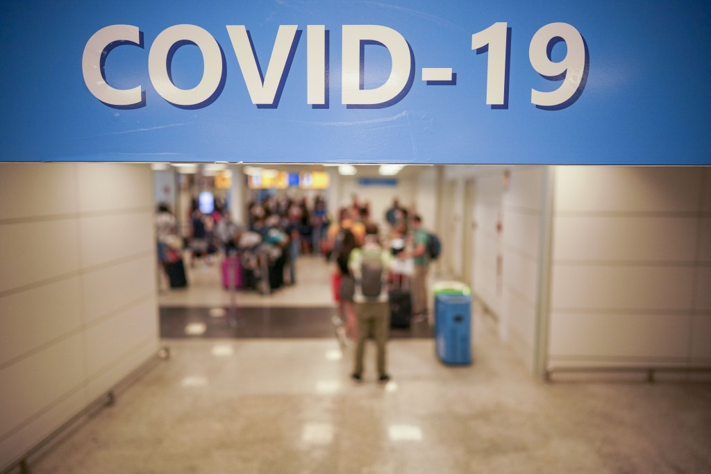 Vacationers arriving in Rome from four Mediterranean countries line up with their suitcases at Rome's Leonardo da Vinci airport to be immediately test...