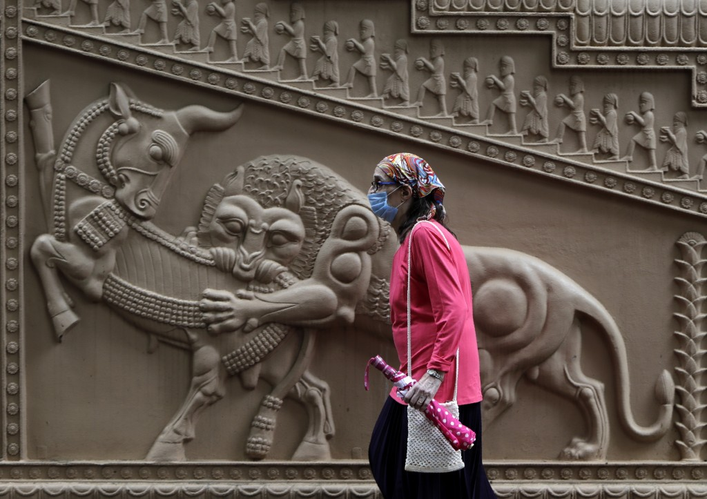 A Parsi woman wearing mask as a precaution against the coronavirus enters a prayer hall near a Fire Temple during Parsi New Year in Mumbai, India, Sun...