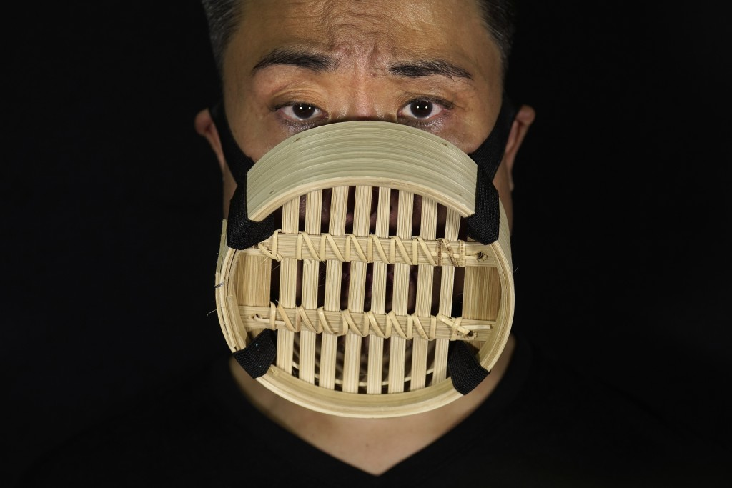 Edmond Kok, a Hong Kong theater costume designer and actor, wearing a face mask made from Chinese bamboo steamer in Hong Kong Thursday, Aug. 6, 2020. ...