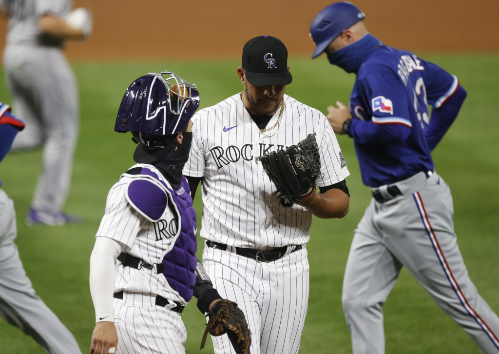 Colorado Rockies catcher Tony Wolters, left, confers with relief pitcher Carlos Estevez after he retired Texas Rangers' Jose Trevino to end the top of...