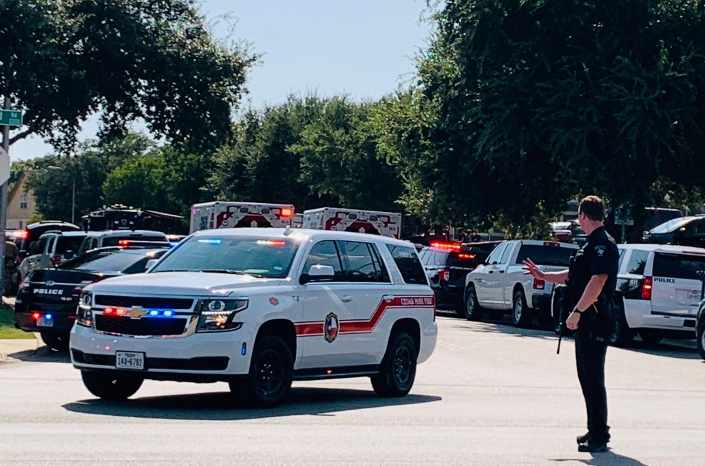 Police and other emergency vehicles are gathered near where three police officers were shot Sunday, Aug. 16, 2020, and a person remained barricaded in...