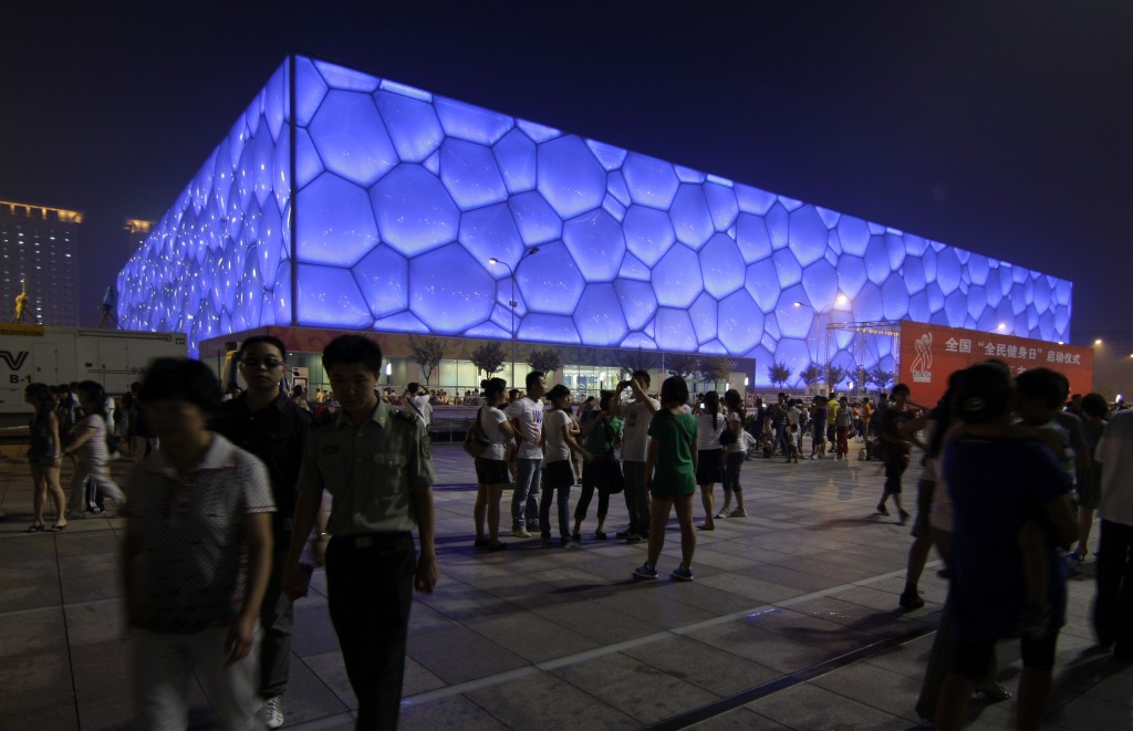 File-Visitors walk past the National Aquatics Center, known as the Water Cube, on the eve of the one-year anniversary of the opening of the Olympic Ga...