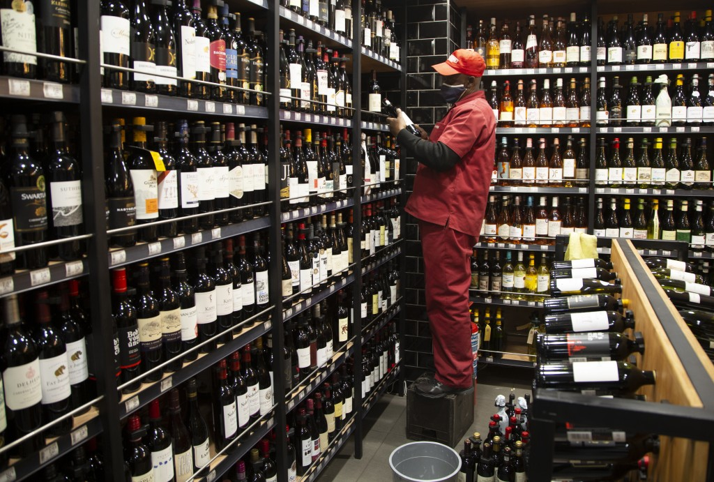 A man stocks shelves with bottles of wine at a Johannesburg liquor store in Johannesburg Monday, Aug. 17, 2020, as the country will lift its coronavir...