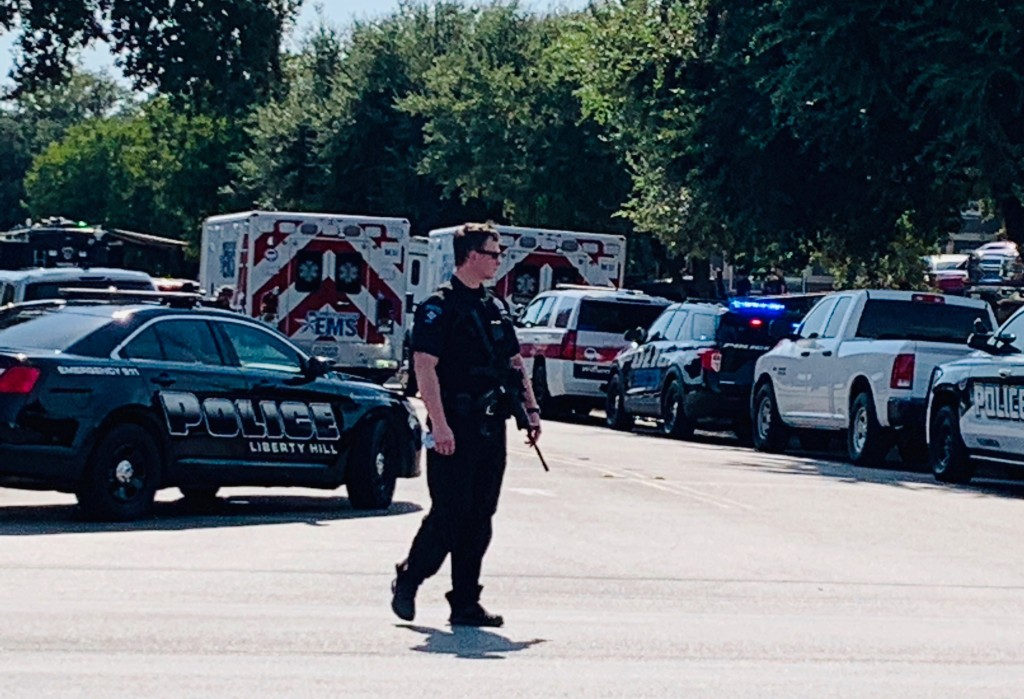 A police officer stands on a street near where emergency vehicles are gathered near where three police officers were shot Sunday, Aug. 16, 2020, and a...