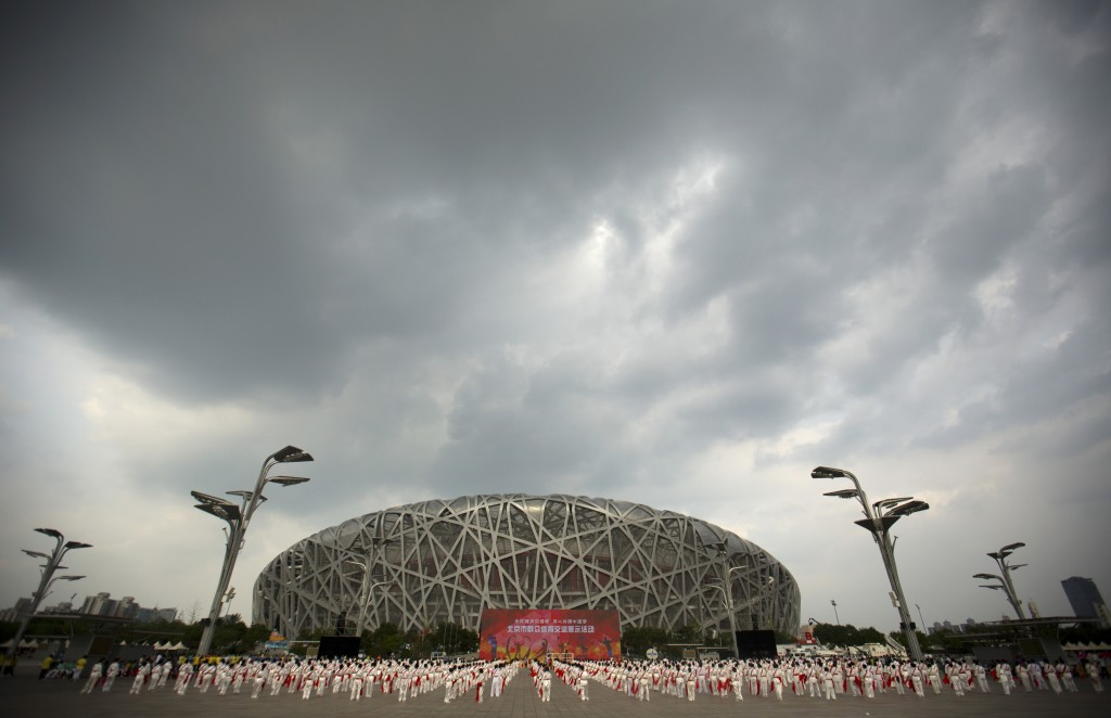 File-Participants dance under threatening skies at a gathering to watch the announcement of the 2022 Winter Olympics host city outside the Beijing Oly...