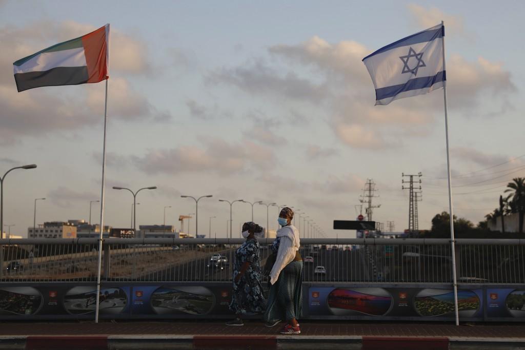 Women wearing face masks against the coronavirus walk past United Arab Emirates and Israeli flags at the Peace Bridge in Netanya, Israel, Sunday, Aug....